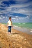 走在海滩垂直的小男孩 免版税库存照片
