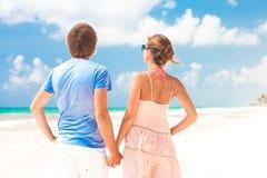 走在海滩微笑的年轻愉快的夫妇。 免版税库存照片