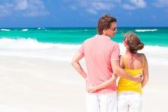 走在海滩微笑的年轻愉快的夫妇。 库存图片
