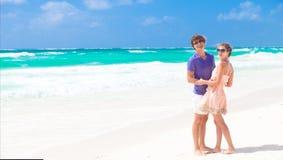 走在海滩微笑的年轻愉快的夫妇。 图库摄影