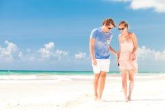 走在海滩微笑的年轻愉快的夫妇。 免版税库存图片