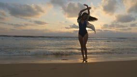 走在海滩海洋和盆射水的愉快的妇女与她的脚 享有生活的年轻美丽的女孩 图库摄影