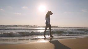 走在海滩海洋和盆射水的愉快的妇女与她的脚 享有生活的年轻美丽的女孩 免版税图库摄影