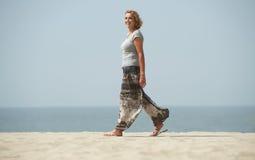 走在海滩的一名成熟妇女的画象 免版税库存照片