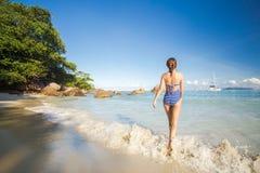 走在海滩的一名美丽的妇女 免版税库存照片