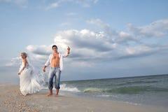 走在海滩的一对已婚夫妇 免版税库存照片
