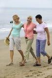 走在海滩的三名妇女 库存图片
