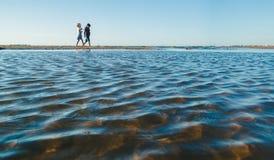 走在海滩的两个女孩 免版税库存图片