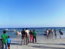 走在海滩的人们在印度洋蒙巴萨 免版税库存图片