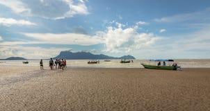 走在海滩的人们有小船从Bako国家公园返回在婆罗洲 免版税库存照片
