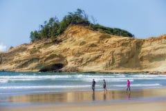 走在海滩的兄弟姐妹在俄勒冈海岸的和平的城市 免版税库存照片