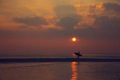 走在海滩的冲浪者女孩 免版税库存照片