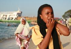 走在海滩的回教黑人女孩在桑给巴尔附近港  免版税库存照片