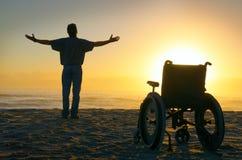 走在海滩的奇迹精神愈合的被致残的人在sunri