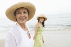 走在海滩的妇女和女儿 免版税图库摄影