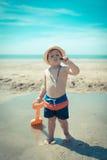 走在海滩的小男孩孩子检查壳 免版税库存照片