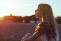 走在海滩的少妇在日落光下, 库存照片