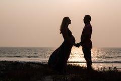 走在海滩的怀孕的夫妇 免版税库存照片