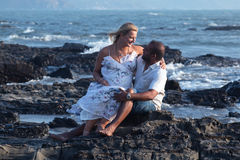 走在海滩的怀孕的夫妇 免版税库存图片