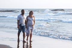 走在海滩的怀孕的夫妇 库存照片