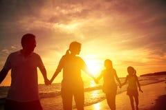 走在海滩的愉快的家庭剪影 免版税库存图片