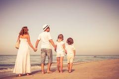 走在海滩的愉快的家庭在天时间 免版税库存图片