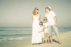走在海滩的愉快的家庭在天时间 库存图片