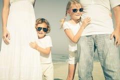 走在海滩的愉快的家庭在天时间 免版税库存照片
