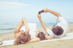 走在海滩的愉快的家庭在天时间 库存照片