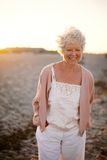 走在海滩的愉快的成熟妇女 免版税库存照片