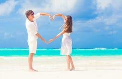 走在海滩的愉快的浪漫年轻夫妇做心脏塑造 免版税库存照片