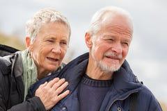 走在海滩的愉快的年长资深夫妇 图库摄影