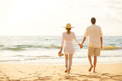 走在海滩的成熟夫妇在日落 免版税库存图片