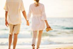 走在海滩的成熟夫妇在日落 免版税图库摄影