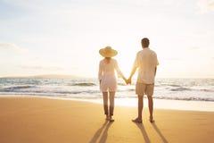 走在海滩的成熟夫妇在日落 免版税库存照片