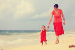 走在海滩的母亲和小女儿 免版税库存图片