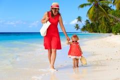走在海滩的母亲和逗人喜爱的矮小的女儿 图库摄影