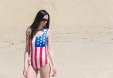 走在海滩的爱国者美丽的妇女在7月 免版税库存图片
