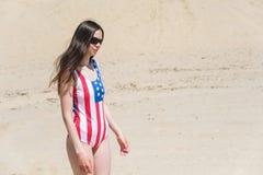 走在海滩的爱国者美丽的妇女在7月 图库摄影