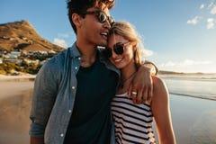 走在海滩的爱恋的年轻夫妇 免版税库存照片