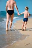 年轻走在海洋的父亲和小儿子靠岸 库存照片