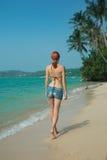 走在海滩的美丽的女孩 免版税库存图片
