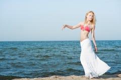走在海滩的美丽的年轻白肤金发的妇女 免版税图库摄影