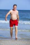 走在海滩的英俊的人 库存图片