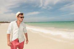 走在海滩的英俊的年轻人, 免版税库存图片