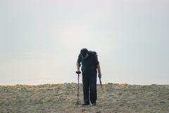 走在海滩金属探测器的人 免版税库存照片