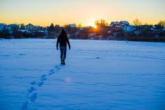 走在深刻的多雪的领域的人 免版税库存图片