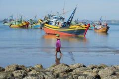 走在渔船背景的沿海小条的越南妇女  美奈,越南钓鱼海港  免版税库存照片