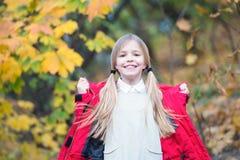 走在温暖的夹克的儿童白肤金发的长的头发室外 女孩愉快在红色外套享受秋天公园好天气 儿童穿戴 免版税库存图片