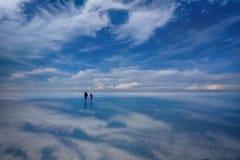 走在湖撒拉族de Uyuni,玻利维亚的人们 免版税库存图片